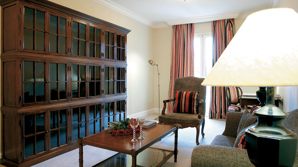 Executive Suite | Spacious living room with the aristocratic styled  bookcase